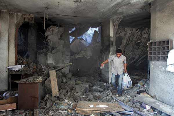 A man gathers his belongings that survived after an Israeli bomb was dropped on his home. Photo courtesy of rinf.com.